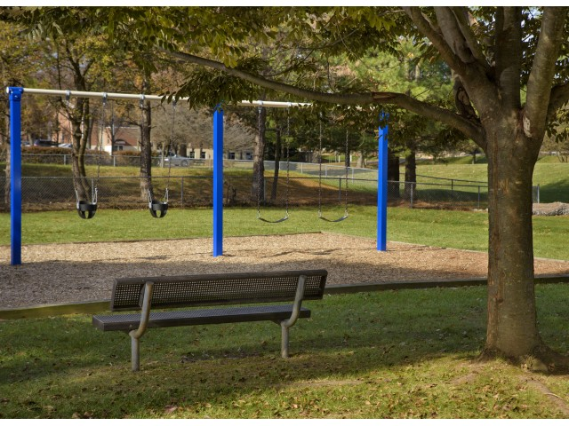 Playground and bench in wooded area at Piney Ridge Apartments & Townhomes.