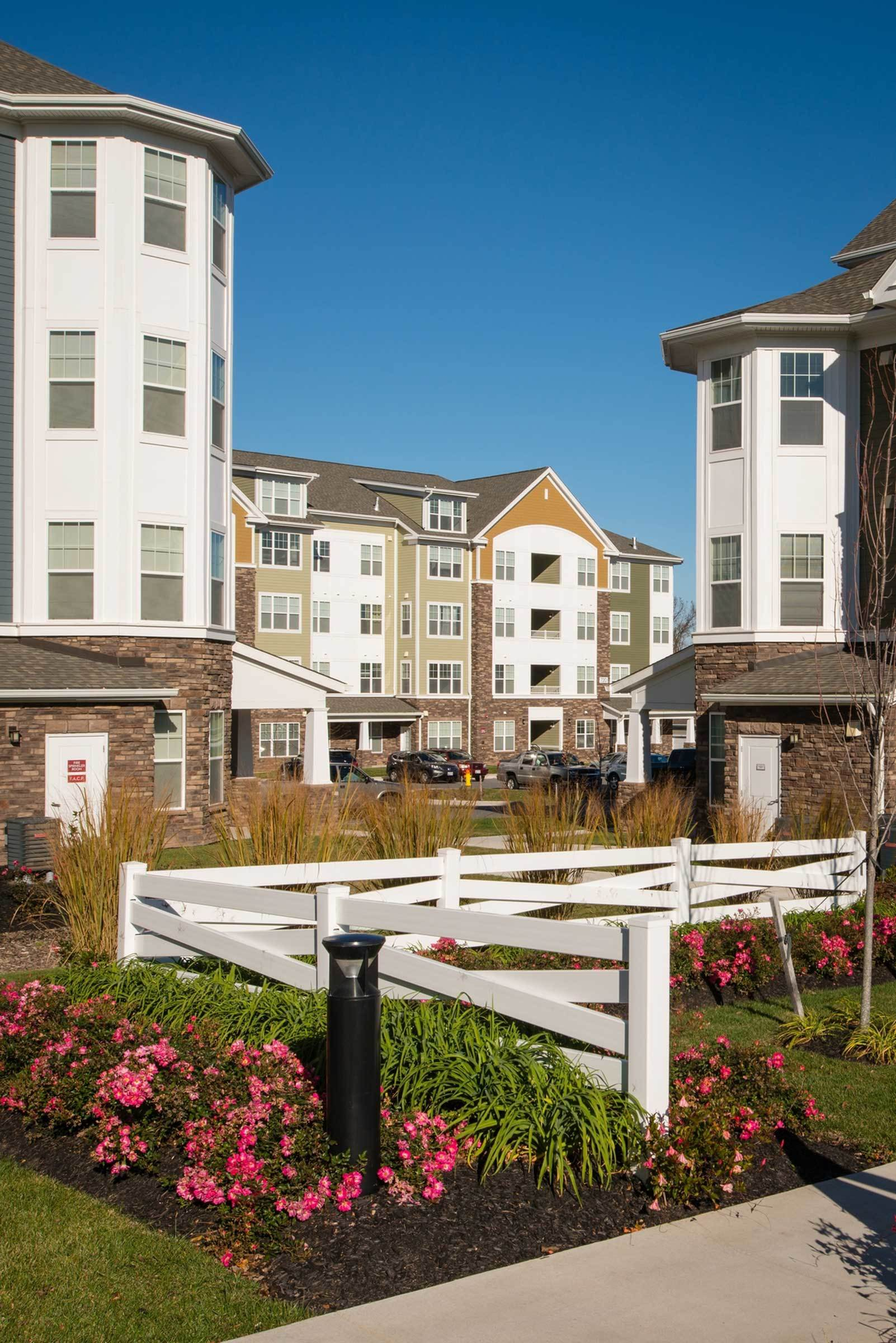 Community view with landscaping, flowers, and view of garden style apartments.