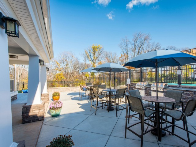 Outdoor dining area with tables and umbrellas outside the clubhouse patio at Prospect Hall Apartments.