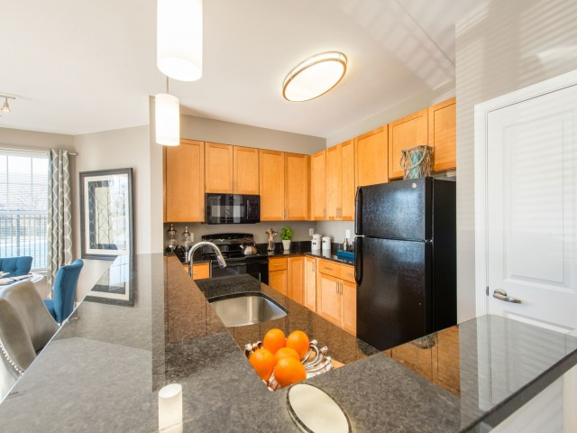 Fully-equipped kitchen with island, pendant lighting, granite countertops, and modern black appliances