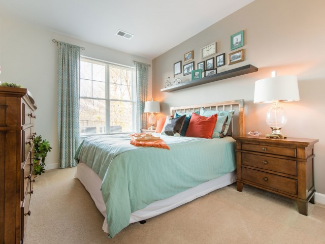 Spacious bedroom with a large window and carpeting at Prospect Hall Apartments