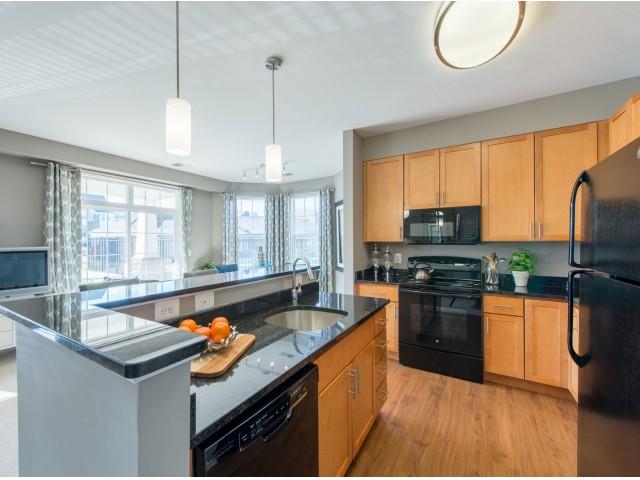 Modern kitchen with vinyl plank flooring, pendant lighting, and black appliances.