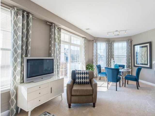 Living room and separate dining area with floor-to-ceiling windows at Prospect Hall Apartments