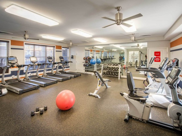 24-hour fitness center with treadmills, yoga balls, free weights, stationary cycles, and other gym equipment.