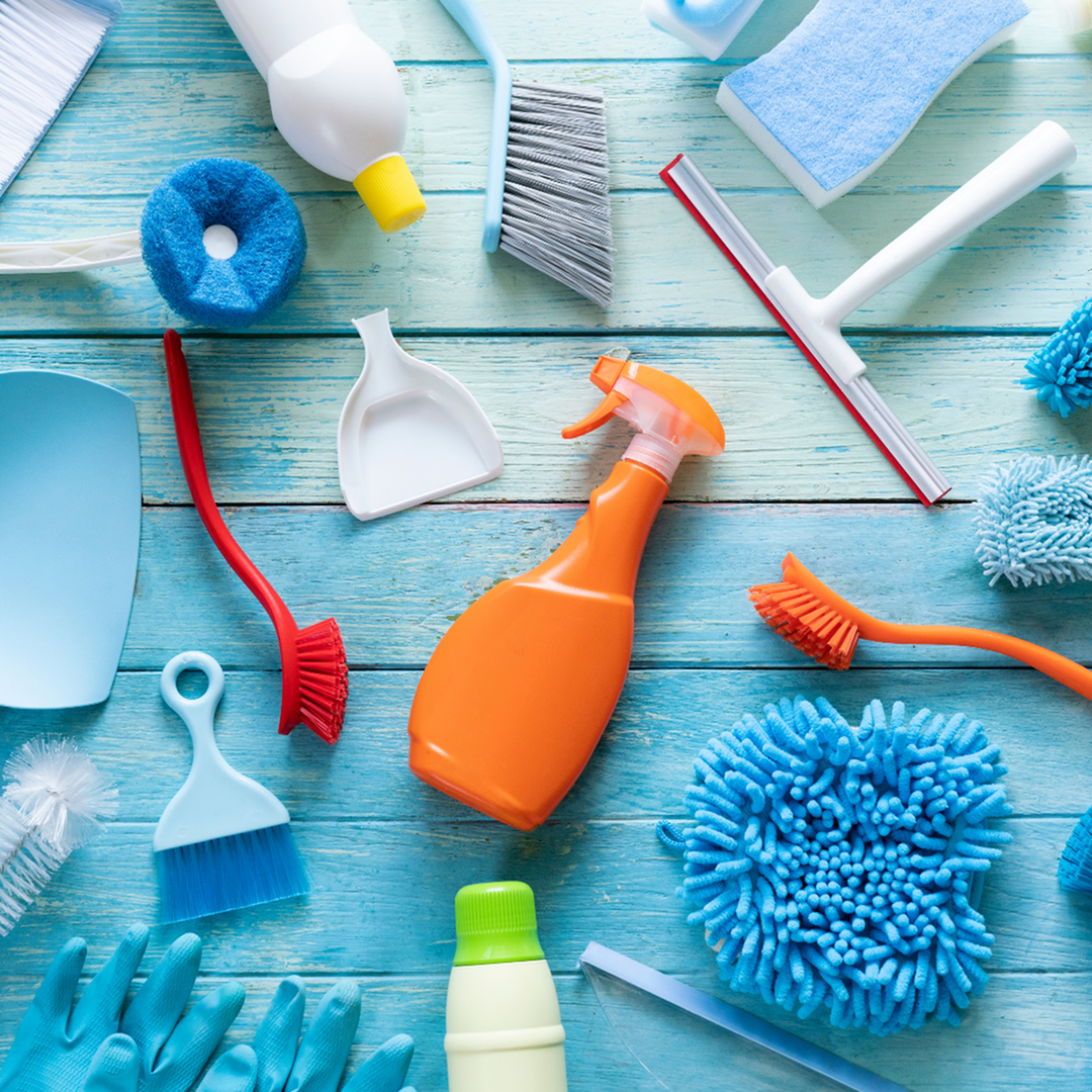 A variety of cleaning supplies are spread out on a blue plank floor.