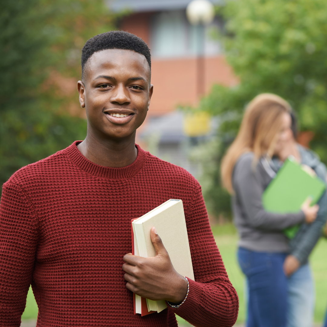 A young African American college student looks at the camera smiling. Other students are in the background talking, but blurred.