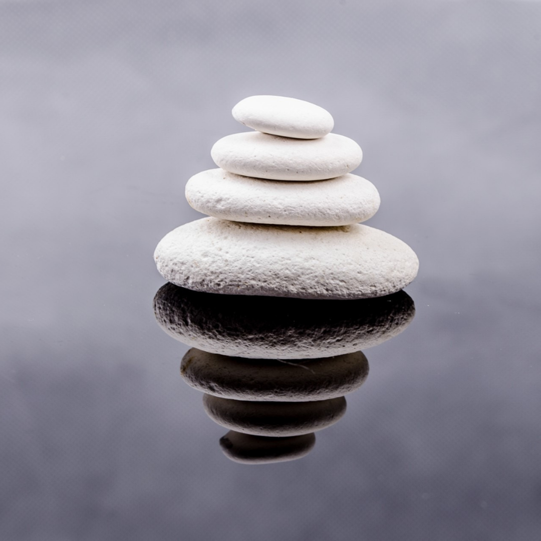 Smooth white stones stacked on still water