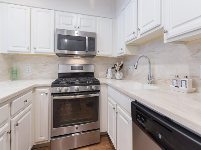Image of Modern kitchen with stainless appliances, including gas range, granite/corian counters and breakfast bar for Christopher Columbus Plaza