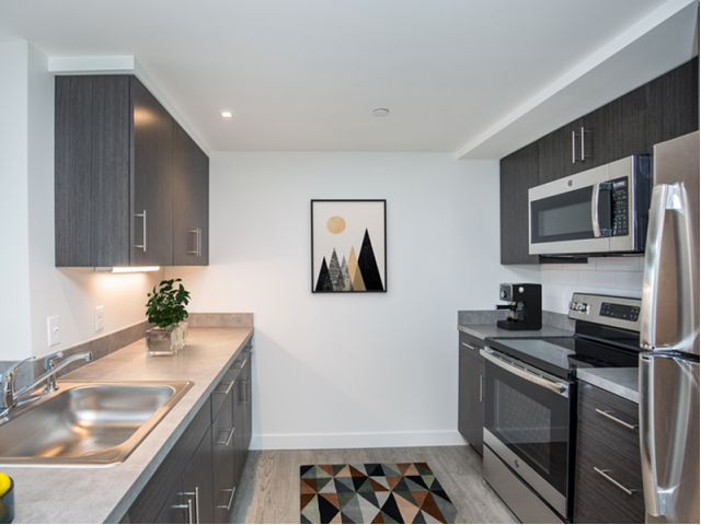 Image of Sleek kitchens with rich dark cabinetry, soft grey solid-surfacing countertops and stainless appliances for Coppersmith Village