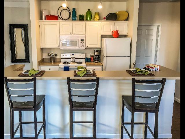 Modern kitchens, including full-size refrigerator, microwave, oven/range, dishwasher, bar stools