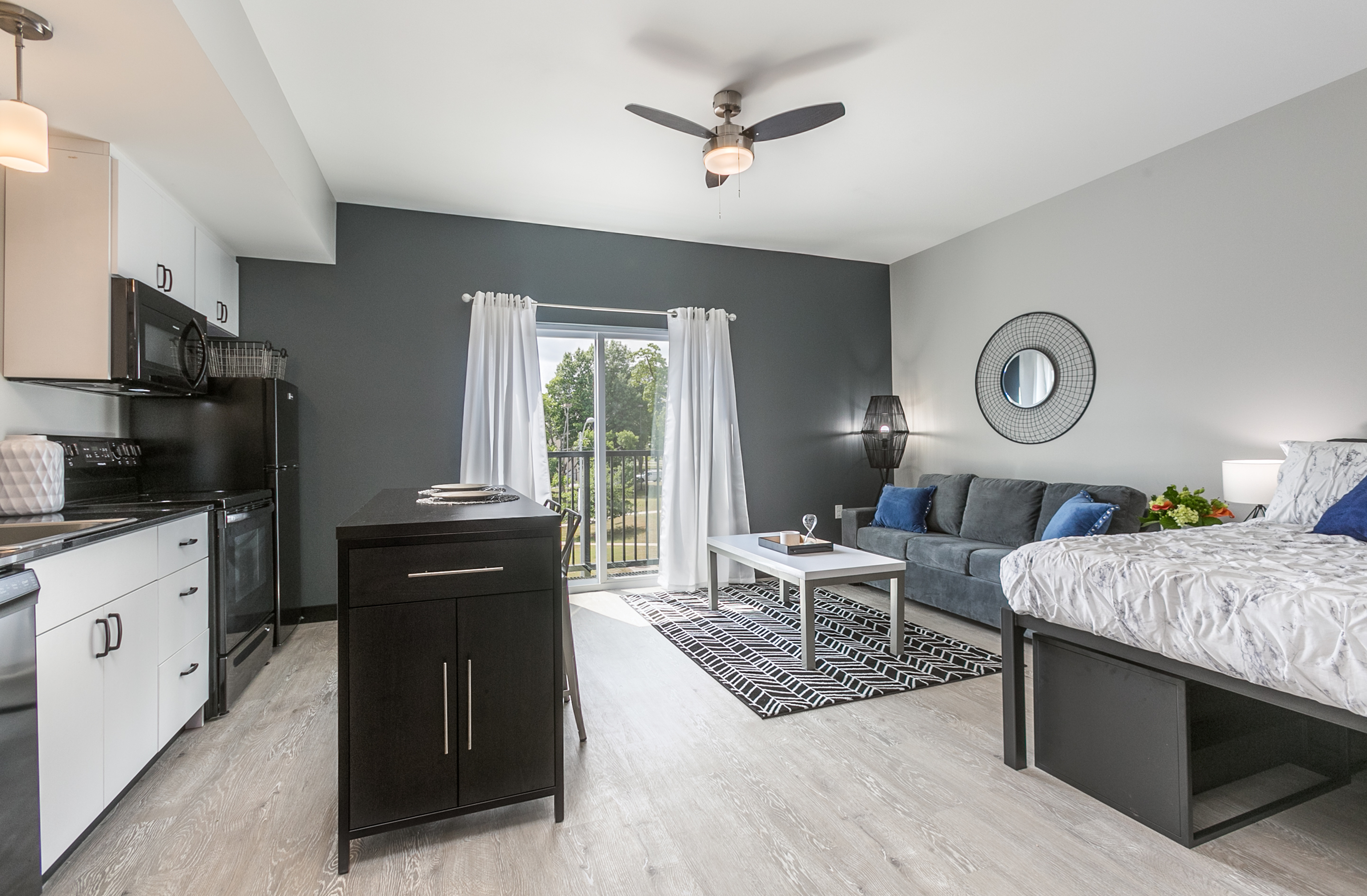 Studio apartment with bed and couch near kitchen