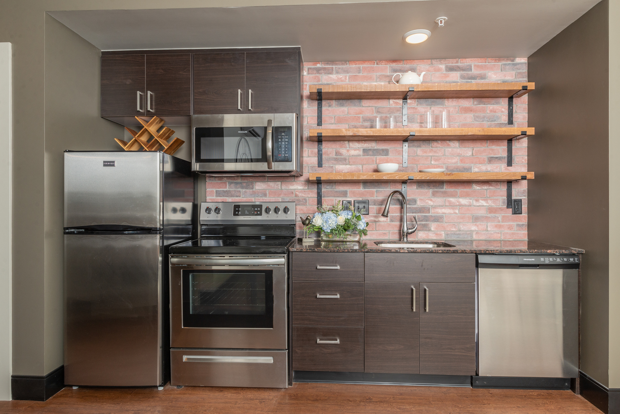 apartment in studio apartment with gray cabinets and exposed brick wall