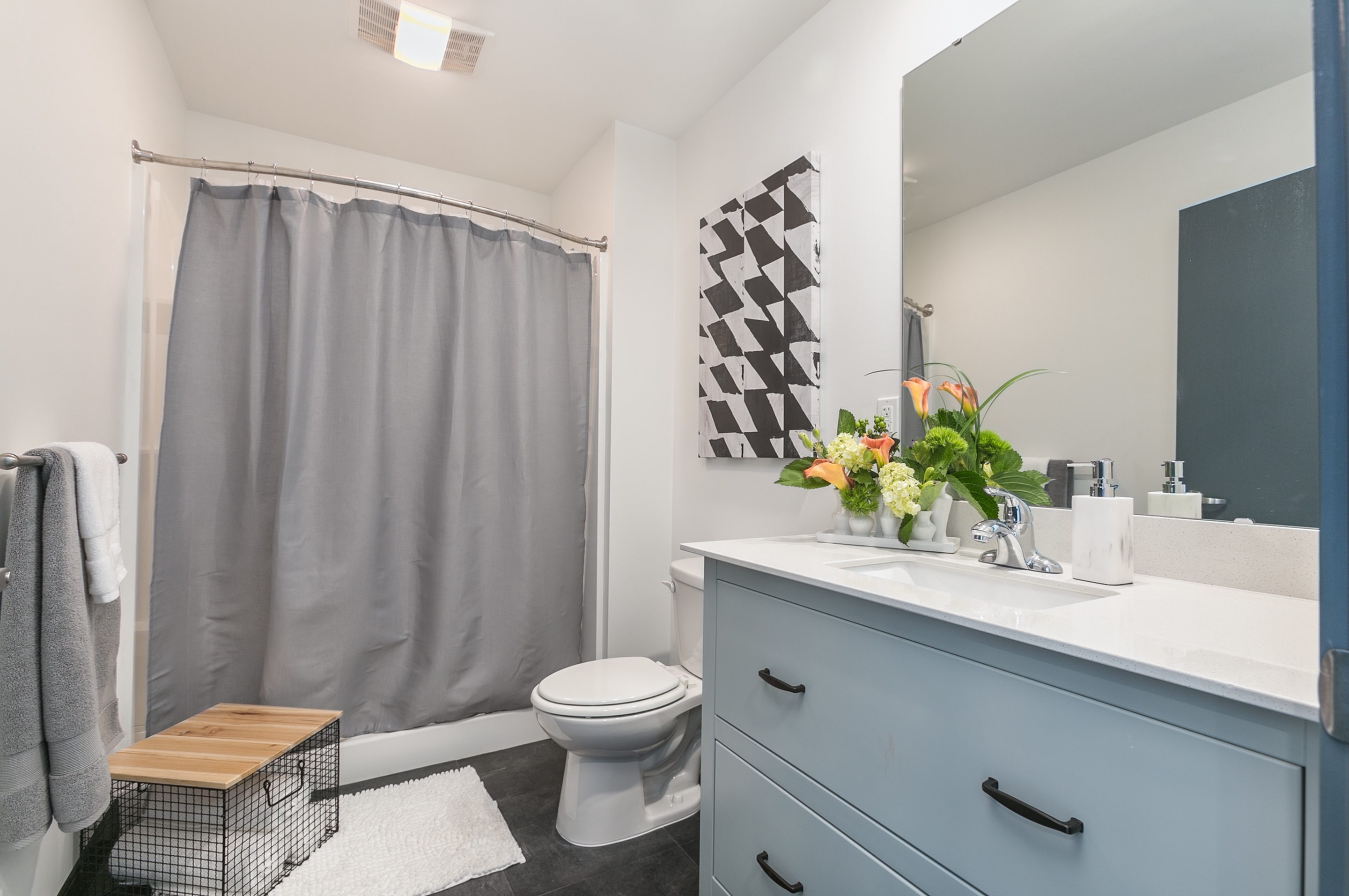 bathroom with blue cabinets and blue shower curtain