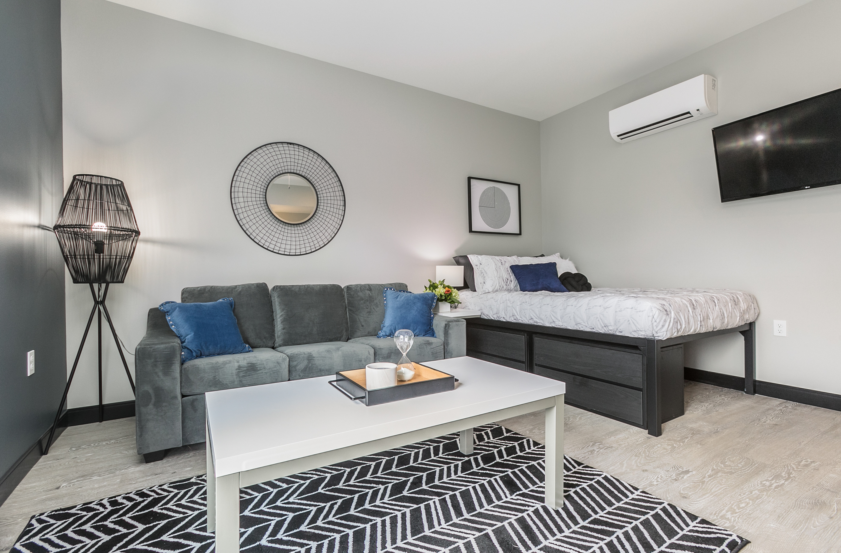 studio apartment with grey couch, bed with white bedspread and a coffee table