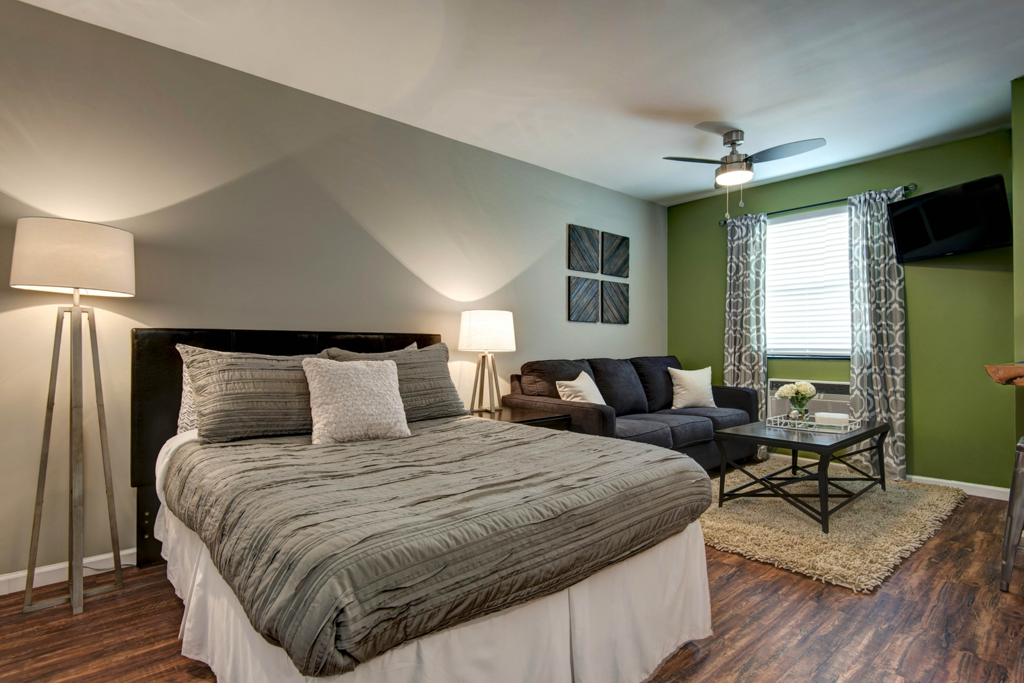 studio apartment with bed with grey bed spread and a blue couch in the living room
