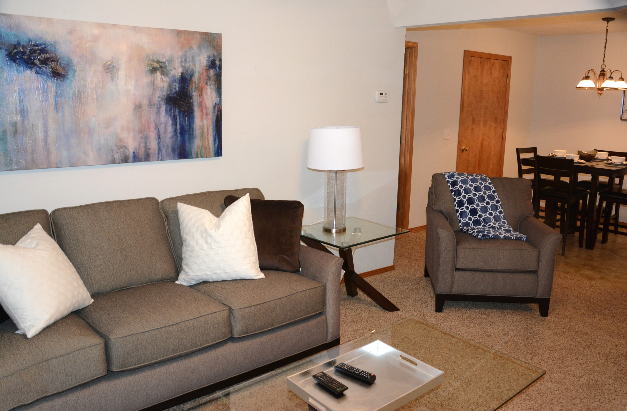 living room with large grey couch and chair and a coffee table