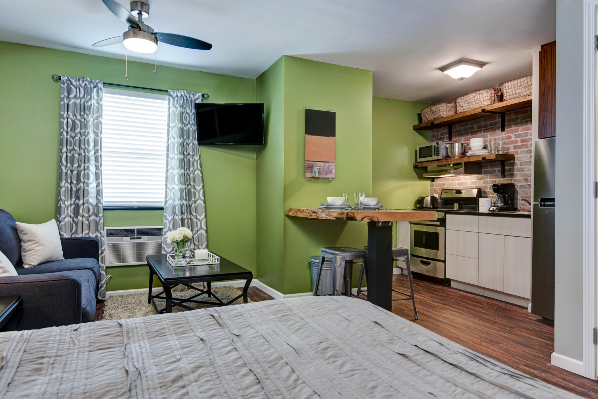 studio apartment with bed, couch and kitchen with exposed brick