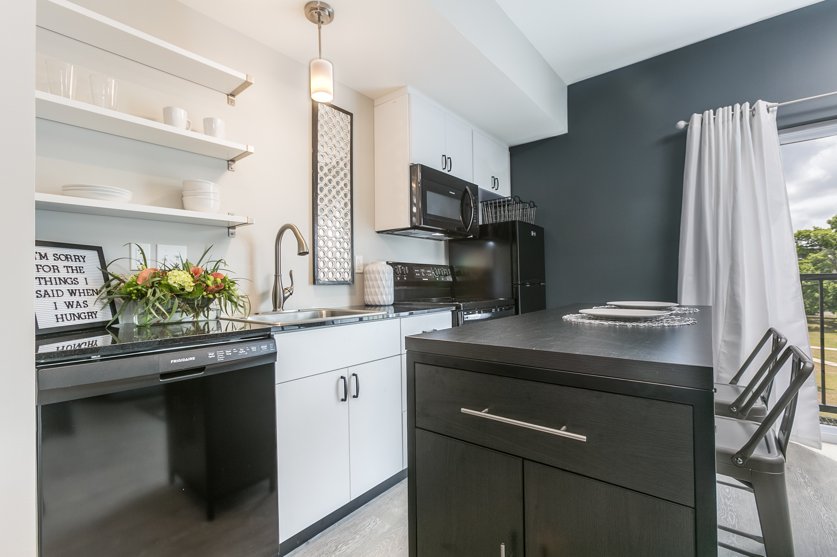 kitchen with white cabinets, black appliances and white floating shelves that holds dishes