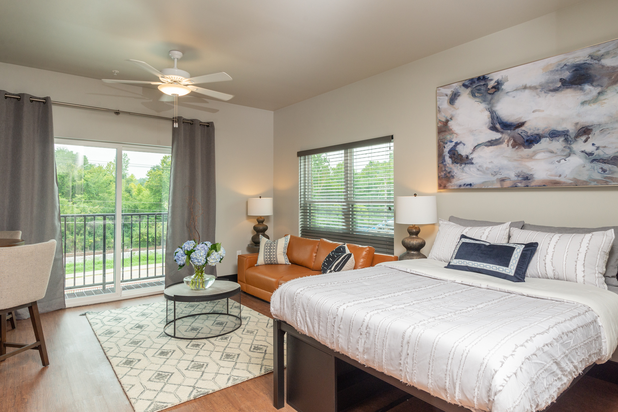 studio apartment with tan couch and a bed with white comforter