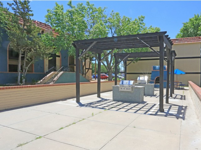 Outdoor Kitchen amenity at Monterra Apartment Homes features 2 full built in gas grills, outdoor wood burning fireplaces and wooden pergola accents.