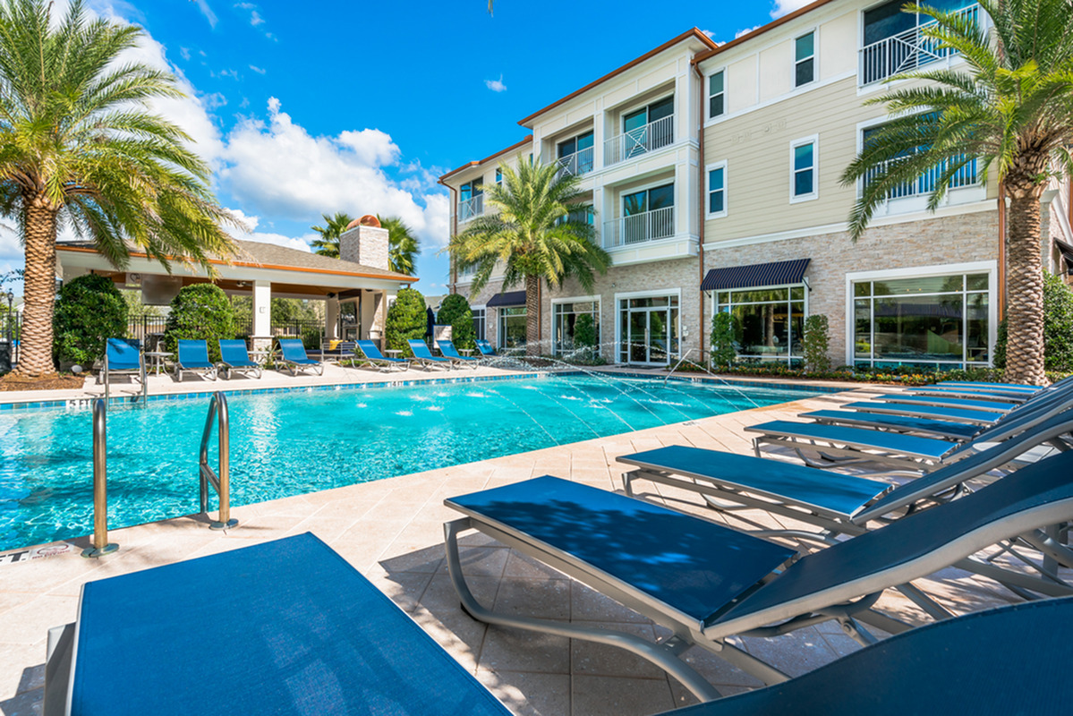 View of Pool Area, Showing Loungers, Palm Trees, Grilling Lounge, and Building at The Marq Highland Park Apartments