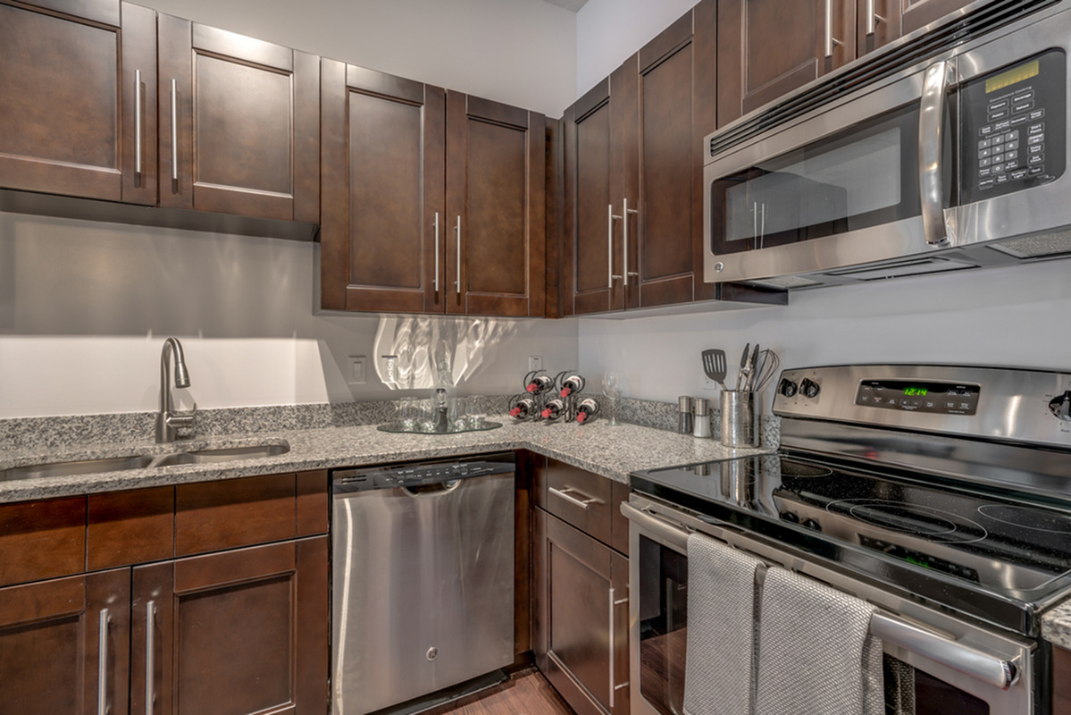 Image of apartment kitchen with custom cabinetry and stainless steel dishwasher, microwave, and stove