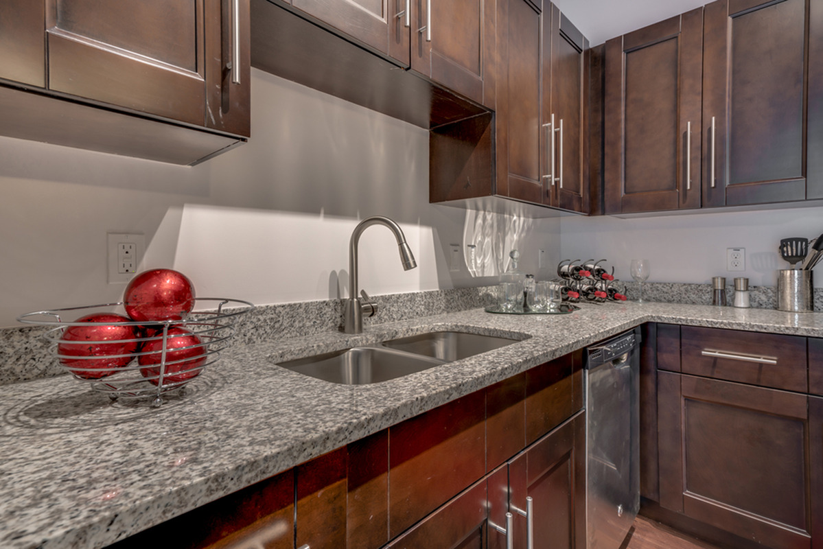 View of Kitchen, Showing Granite Countertop, Custom Cabinetry, and Dishwasher at The Marq Highland Park Apartments