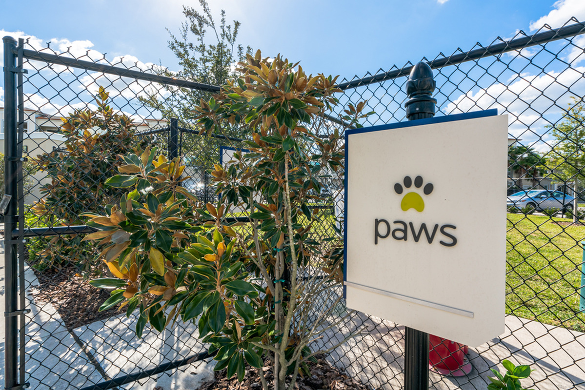 View of Dog Park, Showing Fenced-In Dog Park and Paws Signage at The Marq Highland Park Apartments