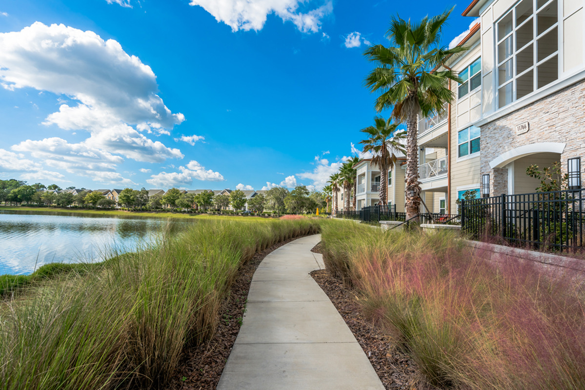 View of Walking Trail, Showing Walking Path, Lake to the Left, and Building Exterior to the Right at The Marq Highland Park Apartments