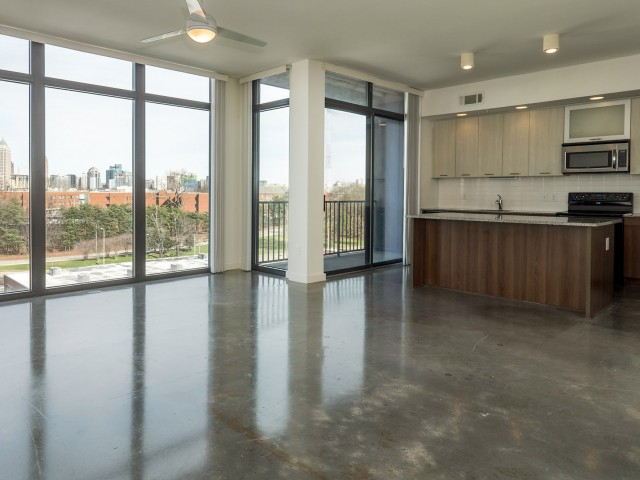 Enjoy Our Stained Concrete Flooring, With View of Island, View of Kitchen, Balconies, and Floor-To-Ceiling Windows at 935M Apartments