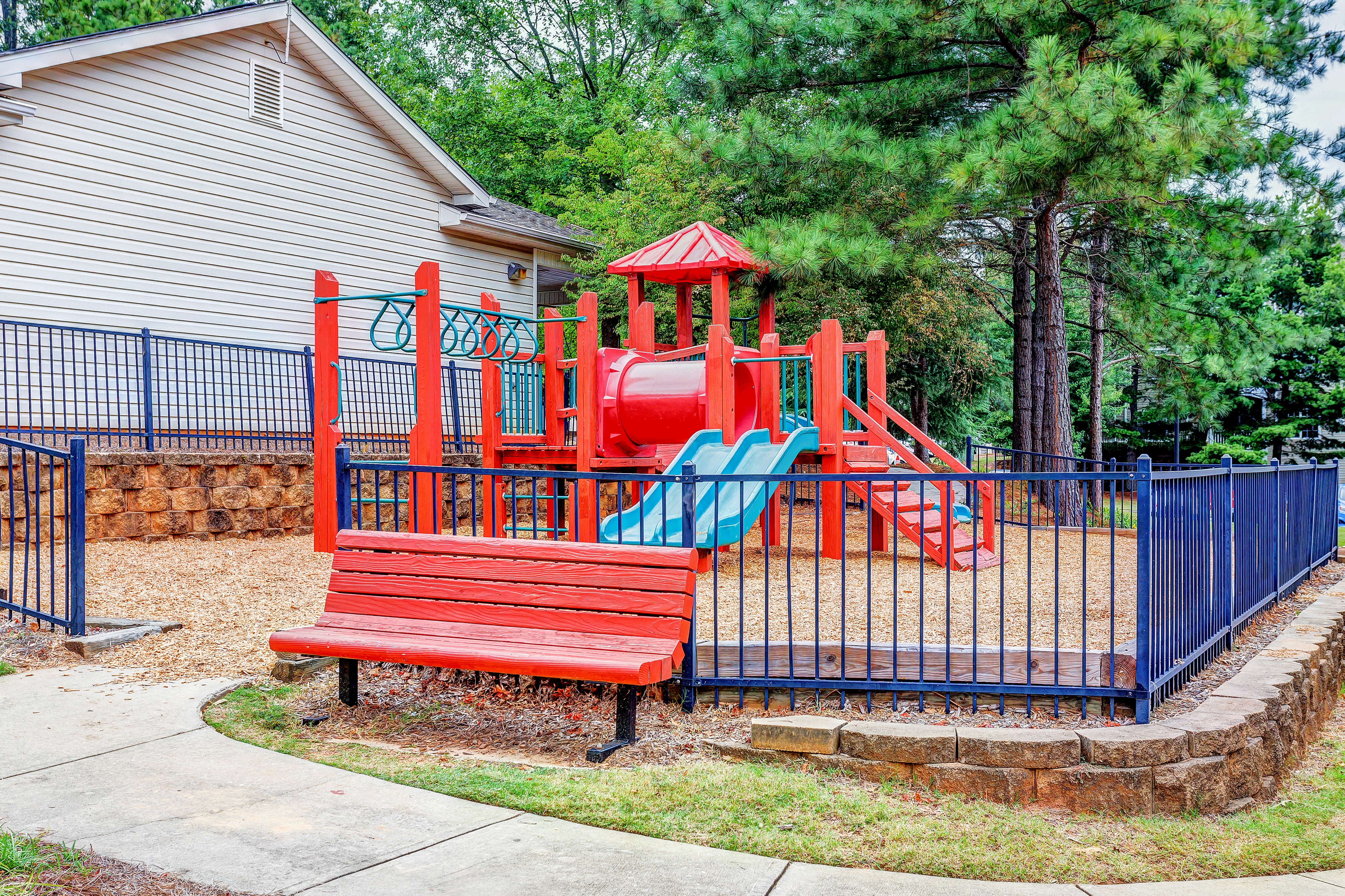 View of Playground, Showing Fenced-In Area, Monkey Bars, and Bench at Summer Park Apartments