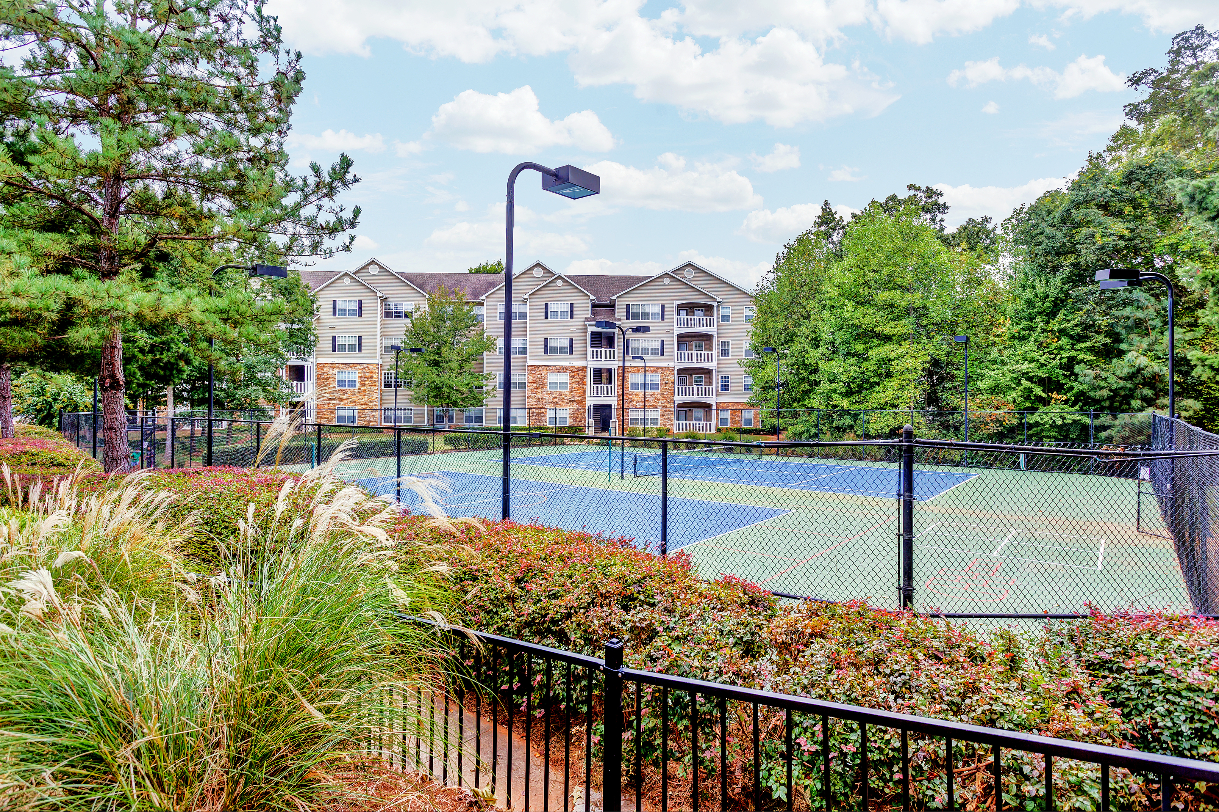 View of Tennis Court, Showing Fenced-In Area and Landscaping at Summer Park Apartments