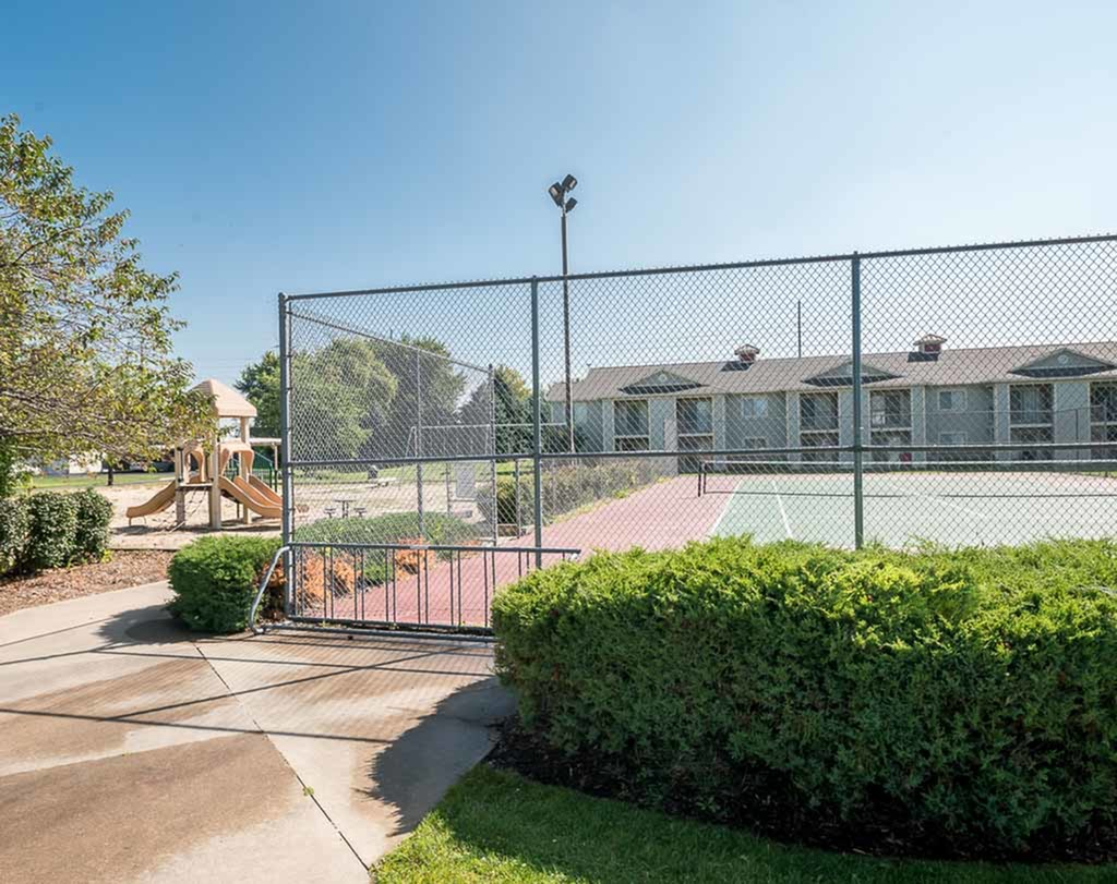 View of Sport Court, Showing Tennis Court, Bike Rack, and Adjacent Playground at Clearview Apartments