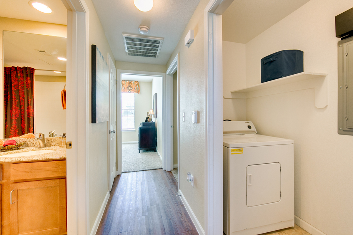View of Laundry Room, Showing Full size Washer, Shelving, and Plank Flooring at Enclave on Golden Triangle Apartments