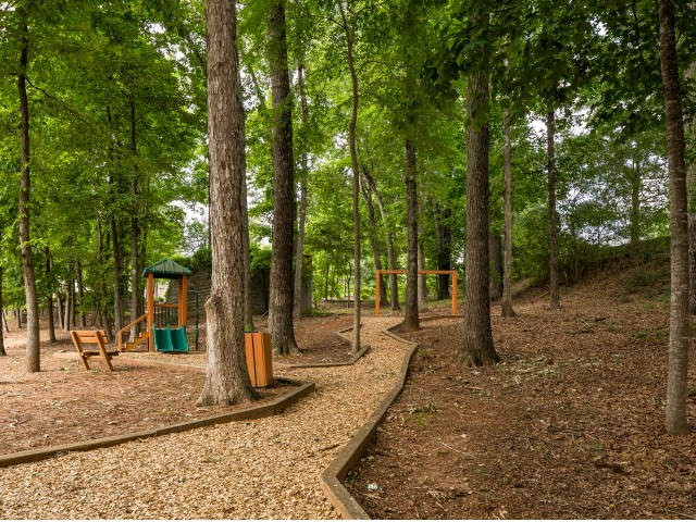 View of Walking Path, Showing Playground and Trees at Retreat at Peachtree City Apartments