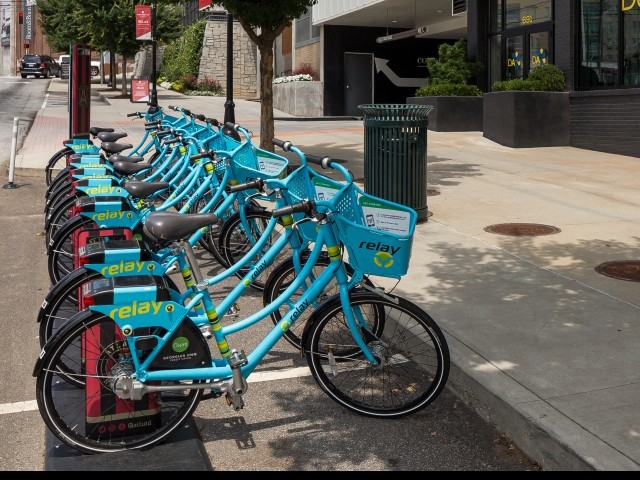Image of blue bicycles, relay bike sharing hub on the outside of Cottonwood Westside