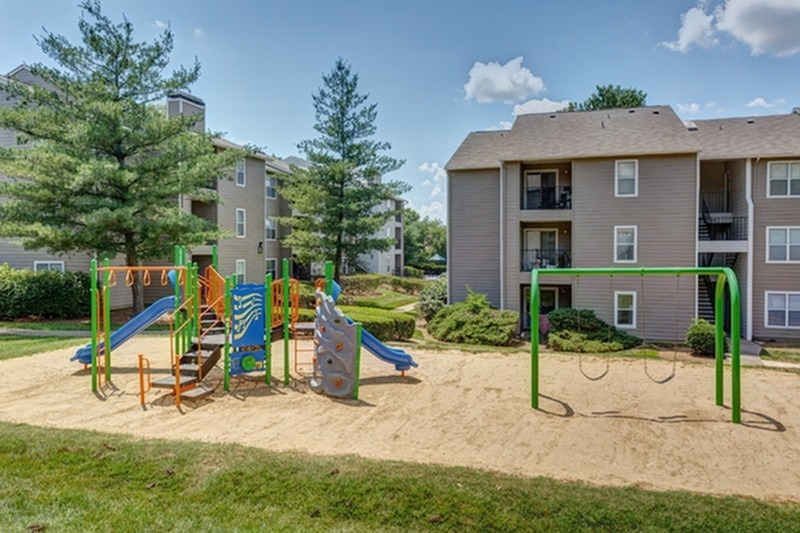 View of Playground, Showing Equipment, Swings, Slides, and Apartment Buildings in Background at 1070 Main Apartments