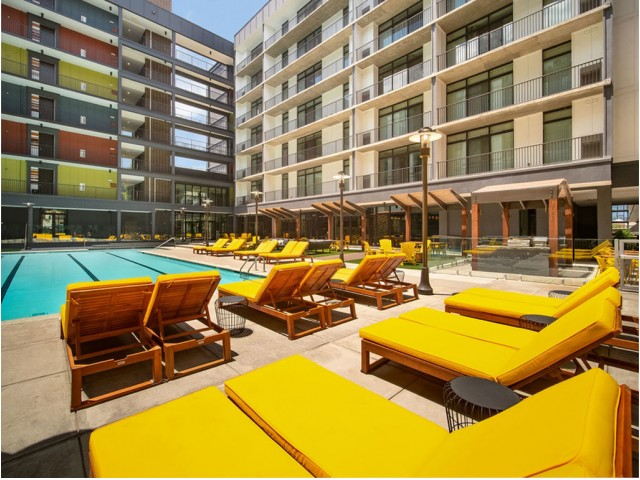 View of Pool Area, Showing Loungers, Grilling Areas, Picnic Tables, and Apartments in Background at 935M Apartments