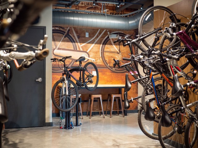 View of Bike Storage, Showing Bikes Hung on Wall, Long Table, and Counter Stools at 935M Apartments