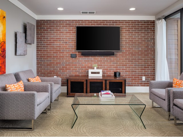 Image of community social space with chairs and mounted flat screen tv on accent brick wall