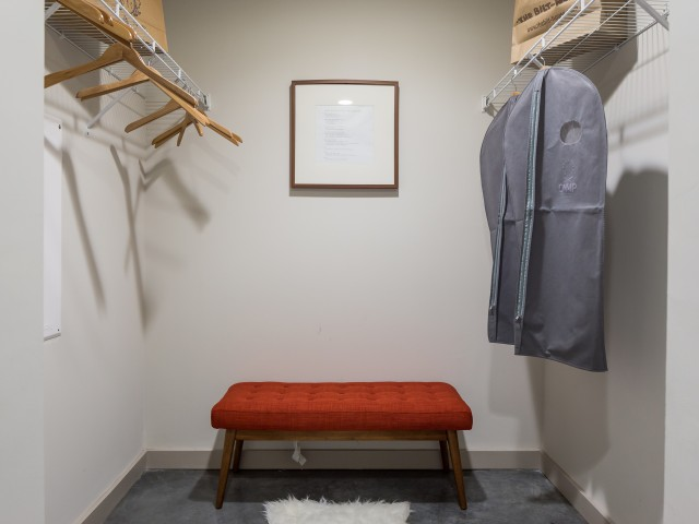 Image of walk-in closet with wooden hangers and bench