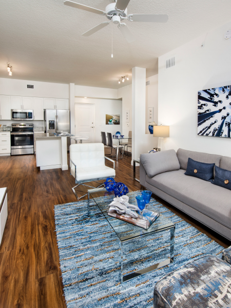 Apartment Interior | Couch, Glass Coffee Table, Accent Chairs, Kitchen and Dining Room | Cottonwood West Palm Apartments
