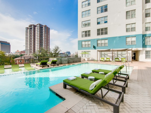 View of Pool Area, Showing Loungers, Cabanas, and View of Apartment Buildings at McKinney Uptown Apartments