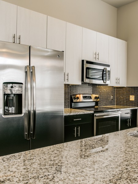 View of the Kitchen at Routh Street Flats Apartments, Showing Granite Countertop and Stainless Steel Appliances