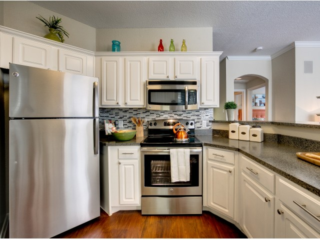 Enjoy Our Upgraded Apartment Homes, With View of Kitchen with Plank Wood Flooring and Stainless Steel Appliances at Stonebriar of Frisco Apartments