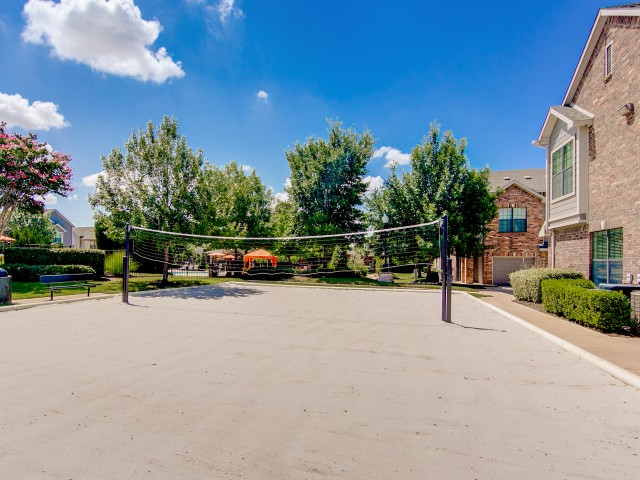 View of Sand Volleyball Court, Showing Net, Benches, and Building Exteriors at Enclave on Golden Triangle Apartments