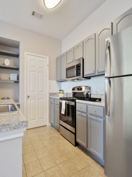 View of the Renovated Apartment Interior at Bluffs at Vista Ridge Apartments, Showing Kitchen With Electric Stainless Appliances and Tile Flooring