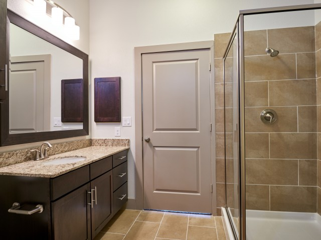 Enjoy Our Bathroom, With View of Granite Countertop, Single Vanity, and Walk-In Shower at 3800 Main Apartments