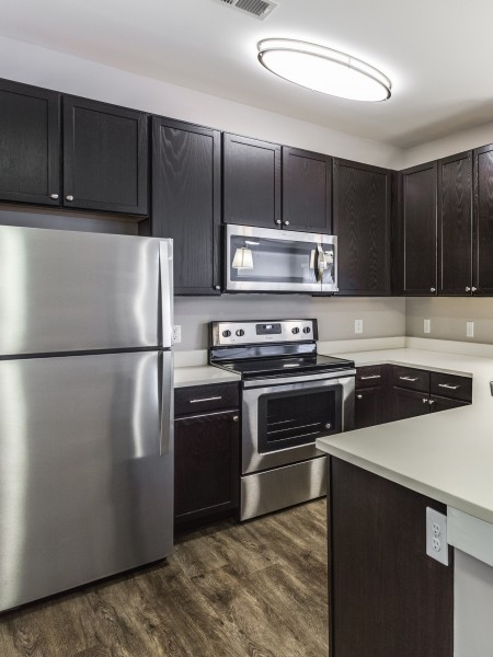 View of the Renovated Apartment Interior at Cottonwood Reserve Apartments, Showing Kitchen, Plank Flooring, and Granite Style Counters