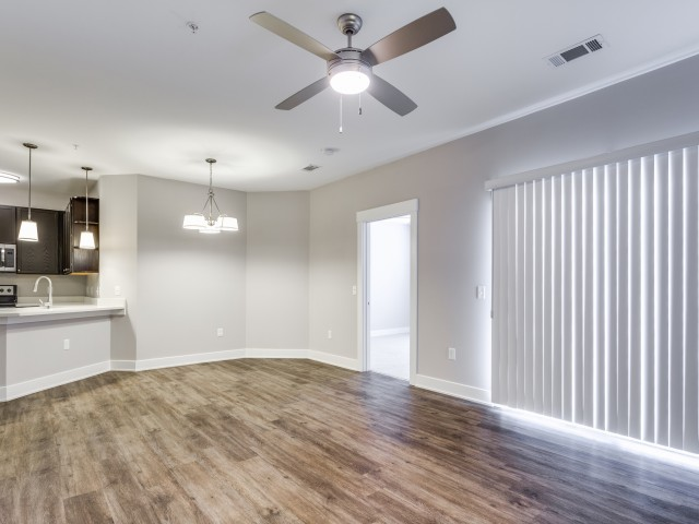 Enjoy Our Vinyl Wood Plank Flooring, With View of Ceiling Fan and Wide Window With Blinds at Cottonwood Reserve Apartments